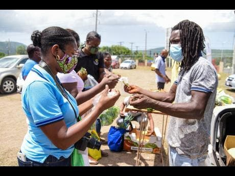 Farmer from East Kirkland Heights, St Andrew, Glenroy Crossman (right), collects money from patron, Denisha Bourne, during a farmers' market last Friday at the Agriculture Ministry's playing field in Mona.