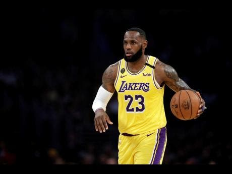 In this March 10, 2020 file photo, Los Angeles Lakers' LeBron James (23) dribbles during the first half of an NBA basketball game against the Brooklyn Nets in Los Angeles.