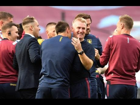Aston Villa's head coach Dean Smith, second right hugs his assistant manager John Terry, as the team celebrates on the pitch after the English Premier League match between West Ham United and Aston Villa at the London Stadium in London, Sunday, July 26, 2020.