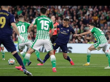 FILE Real Madrid's Mariano Diaz fights for the ball against Betis' Marc Bartra (right) during a La Liga match at the Benito Villamarin stadium in Seville, Spain, on Sunday, March 8.