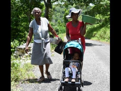 Brenda Simms (left), her daughter Nackiesha Robinson (right), and baby Amora Cramwell walk home from their field in Sturge Town, St Ann, on Tuesday.