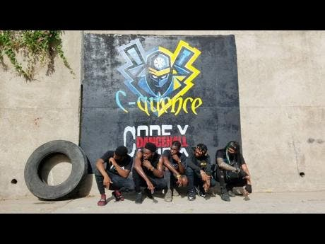 Members of Code X and C-Quence dance groups pose before their joint sign.