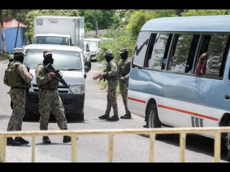 Members of the Jamaica Defence Force check motorists at one of several checkpoints erected in the Sandy Bay community in Clarendon on Thursday. A 14-day lockdown has been imposed on the community following several positive COVID results.