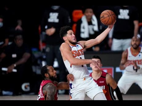 AP Phoenix Suns' Devin Booker goes to the basket over Miami Heat's Andre Iguodala (left) and Tyler Herro (right) during the second half of an NBA basketball game on Saturday, August 8, in Lake Buena Vista, Florida.