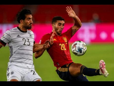 Germany's Emre Can (left) duels for the ball with Spain's Ferran Torres during the UEFA Nations League  match at the Mercedes-Benz Arena stadium in Stuttgart, Germany yesterday
