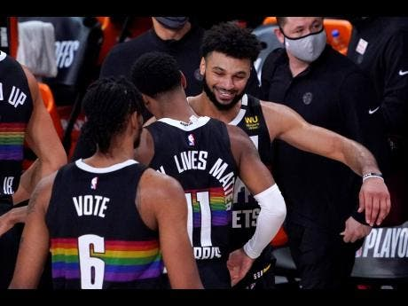 Denver Nuggets' Jamal Murray (right) celebrates with Monte Morris (11) after an NBA conference semi-final play-off basketball against the Los Angeles Clippers yesterday.