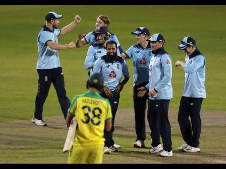 England's Adil Rashid (fourth left) celebrates with teammates after taking the wicket of Australia's Alex Carey to win the second ODI cricket match between England and Australia at Old Trafford in Manchester, England, yesterday.