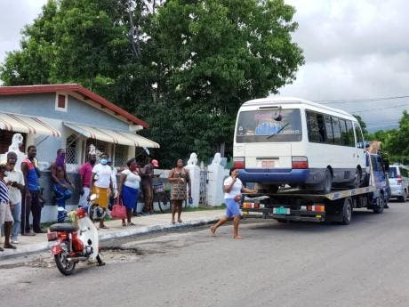 Onlookers peer at the bus in which eight goats were found by St Thomas police on Tuesday.