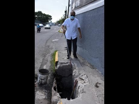 Vivian Blake shows how difficult it is for the visually impaired to navigate around this hole in the sidewalk.