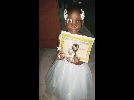 Seven-year-old Abysenya Gordon with her awards from the last prize- giving ceremony.