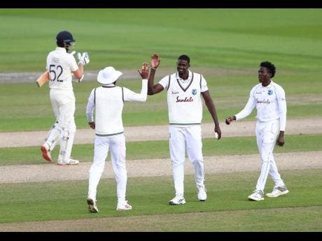 West Indies' captain Jason Holder (second right) celebrates with teammates following the dismissal of England's Dom Sibley (left) on  the third day of the third Test match between at Old Trafford in Manchester, England, on Sunday, July 26.