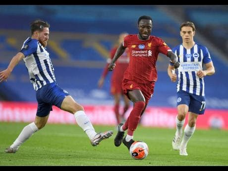 Liverpool's Naby Keita takes the ball past Brighton defenders during a English Premier League match  at Falmer Stadium in Brighton, England, on Wednesday, July 8.