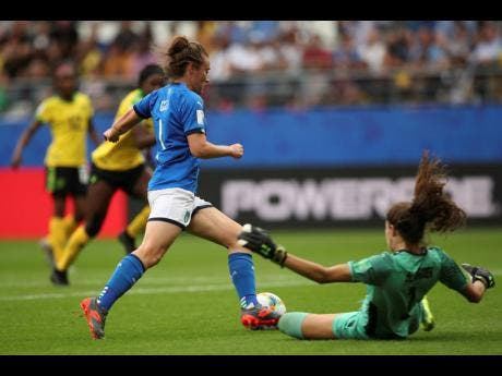 Italy's Aurora Galli ( left) scores her side's fifth goal against Jamaica goalkeeper Sydney Schneider during the Women's World Cup Group C match between Italy and Jamaica at the Stade Auguste-Delaune in Reims, France, Friday, June 14, 2019.