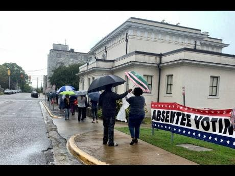 People wait  in the rain to vote in Montgomery, Alabama, last Saturday. Alabama Secretary of State John Merrill said a record number of absentee ballots have already been cast this year in the election. Some counties allowed Saturday voting for the first time.