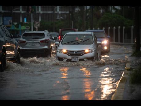 Motorists navigate through a flooded Trafalgar Road in St Andrew on Sunday.