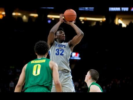 In this November 12, 2019 file photo, Memphis centre James Wiseman shoots in front of Oregon guards Will Richardson (left) and Payton Pritchard during the second half of an NCAA college basketball game.