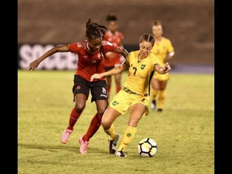 Trinidad and Tobago's Patrice Superville (left) challenges Jamaica's Chinyelu Asher in a Concacaf Championships match in 2018.