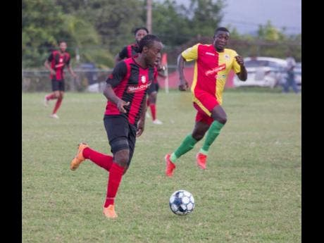 File Kemal Malcolm of Arnett Gardens moves away from Humble Lion's Gregory Lewis during their RSPL encounter at Effortville in Clarendon on December 29, 2019.