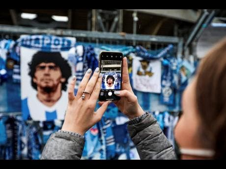 A fan takes pictures of the memorabilia hanging on the gates of the San Paolo stadium in Naples, Italy, yesterday.