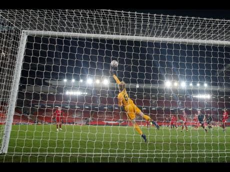 Liverpool's goalkeeper Caoimhin Kelleher saves as he tips the ball over the goal during the Champions League group D soccer match between Liverpool and Ajax at Anfield stadium in Liverpool, England, yesterday.