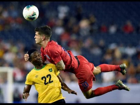 United States midfielder Christian Pulisic  heads the ball above Jamaica midfielder Devon Williams during the second half of a Concacaf Gold Cup semi-final match on Wednesday, July 3, 2019.