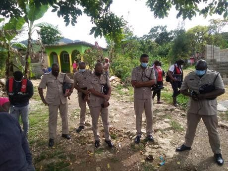 Senior lawmen in a sombre mood at the crime scene in Trelawny where four-year-old Cloey Brown was shot and killed.