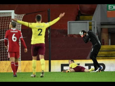 Liverpool's goalkeeper Alisson, right, reacts after giving out a penalty to Burnley's Ashley Barnes.