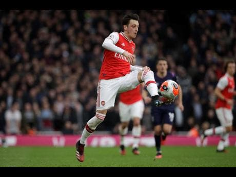 FILE Arsenal's Mesut Ozil controls the ball during the Premier League soccer match against West Ham at the Emirates Stadium in London on Saturday, March 7, 2020.