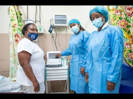 Sister Janice Daley (left), acting maternity ward manager, Savanna-la-Mar Hospital, and Tanesia Tomlinson (right), hospital administrator speak with Carla Drummond, branch manager, Sagicor Bank, Savanna-la-Mar branch, about the benefits of a newly donated patient monitor. The equipment was among items donated to the hospital's maternity ward from funds raised in the 2020 staging of the Sagicor Sigma Corporate Run.