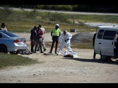Police process the scene where the bodies of Nicholas Neufville and Rahiema Edwards were found yesterday morning in Portmore, St Catherine.