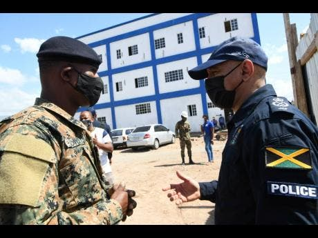 Major General Antony Anderson, the commissioner of police (right), has dialogue with Staff Sergeant Horace Powell of the Jamaica Defence Force during a tour of the new Olympic Gardens Police Station in the St Andrew West Central constituency on February 5.