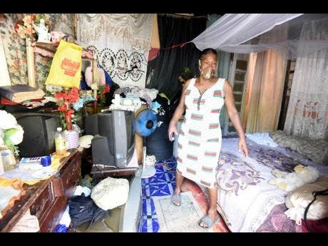 Viviene Smith, shows her bedroom that gets wet whenever it rains due to a leaky roof.