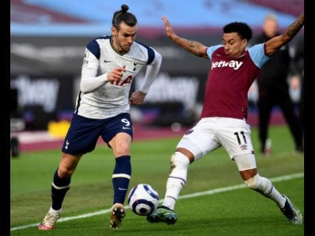 Tottenham's Gareth Bale (left) fights for the ball with West Ham's Jesse Lingard during their English Premier League match  at the London Stadium yesterday.