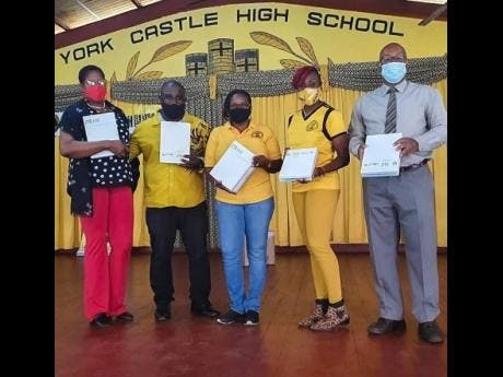 Jennifer Small (second right), president of the York Castle Alumni Association Jamaica chapter, and principal of York Castle High School Raymond Treasure (right) show a few of the donated tablets with (from left) Antoinette Edwards, vice-principal of York Castle High; Michael Riley, vice-president of the local alumni association; and Camille Murphy, secretary of the local alumni association.