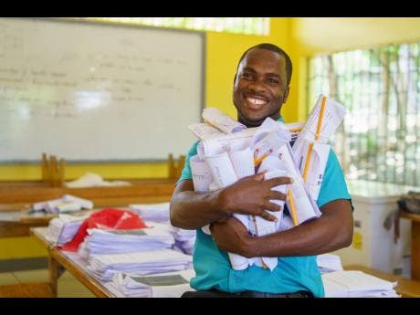 In this file photo, Keron King is getting ready to deliver schoolwork to his students, via bike taxi.