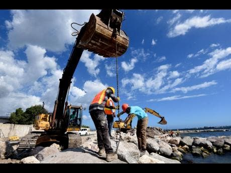 Crewmen working on the newly built seawall in downtown Kingston.