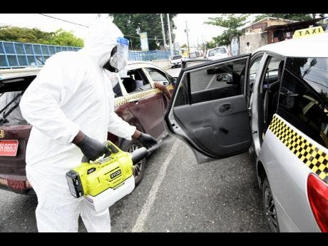Jovan Robinson,  member of Mint Cleaners Ltd. sanitises a taxi in Half-Way Tree, St Andrew, last May.