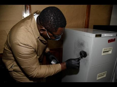 Campbell demonstrates how to dust for fingerprints.