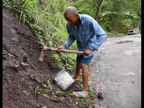 Alley Edwards digs into an embankment for dirt which he uses to fill potholes along the Mount James main road in St Andrew West Rural.