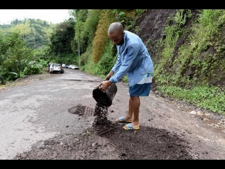 Alley Edwards fills potholes with dirt along the Mount James main road in West Rural St Andrew.
