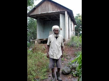 Kenneth Francis in front of the dilapidated house in which he resides.