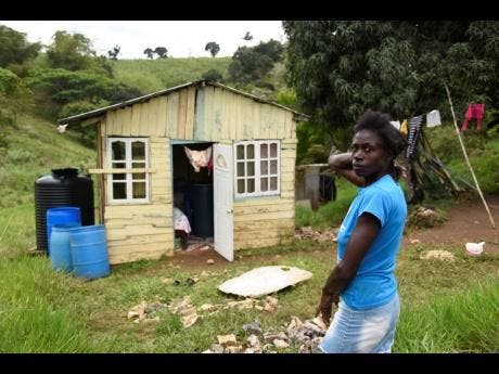 Natasha Rhoden stands in front her one-room board house in Pleasant Hill, Lluidas Vale, St Catherine.