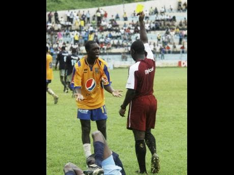 Rusea's Brian Brown (left) is unhappy with the yellow card being shown to him by referee Nicholas Anderson for a foul on Mannings' Asani Samuels during yesterday's Ben Francis KO game at Jarrett Park, in Montego Bay in 2014.