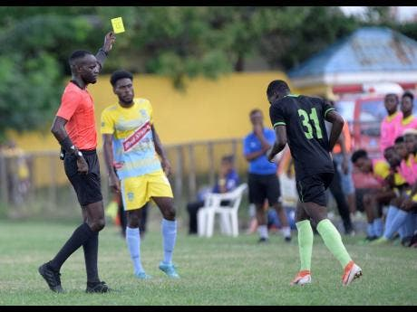 Referee Oshane Nation (left) shows Molynes United's Defender Fakibi Farquharson (right) a yellow card moments after he committed a foul on a Waterhouse player during a Red Stripe Premier League match at the Constant Spring Sports Complex on Sunday, November 3, 2019.