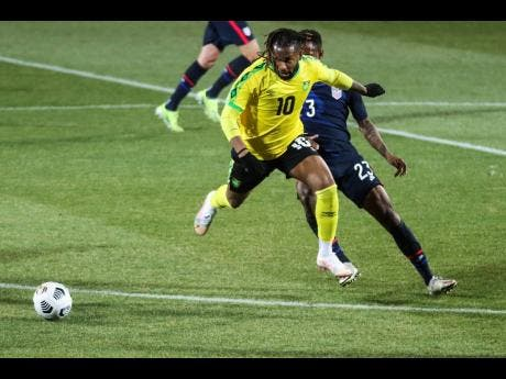Jamaica's Kasey Palmer, foreground, duels for the ball with USA's Kellyn Acosta during  the international friendly soccer match between USA and Jamaica at SC Wiener Neustadt stadium in Wiener Neustadt, Austria, Thursday, March 25, 2021.