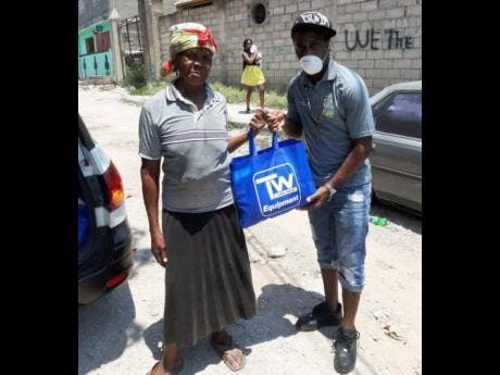 Tremaine Stewart hands resident of Waterhouse Audrey Robinson a care package in the heights of the coronavirus pandemic in the summer of 2020.
