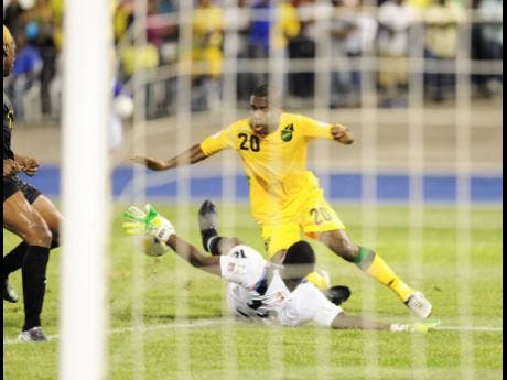 Jamaica's Tremaine Stewart moves past Antigua and Barbuda's goalkeeper Molvin James during a World Cup qualifier at the National Stadium in 2012.
