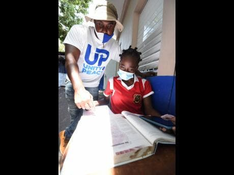 Alphanso Spencer helps Meloney Hinds, fourth form student at Kingston Technical High School, with her schoolwork.