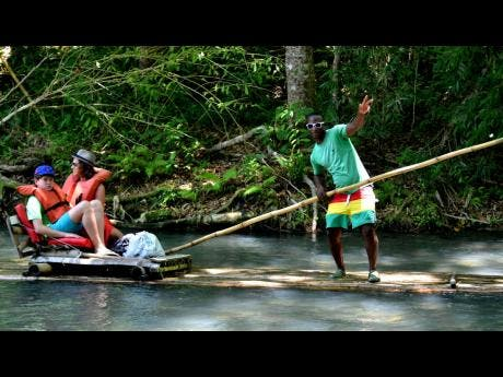 In this 2019 photo, a raft captain takes tourists on a trip down the Martha Brae River.
