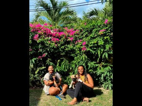 Donice Creary (left) and Nailah Bishop enjoy the company of two pups.